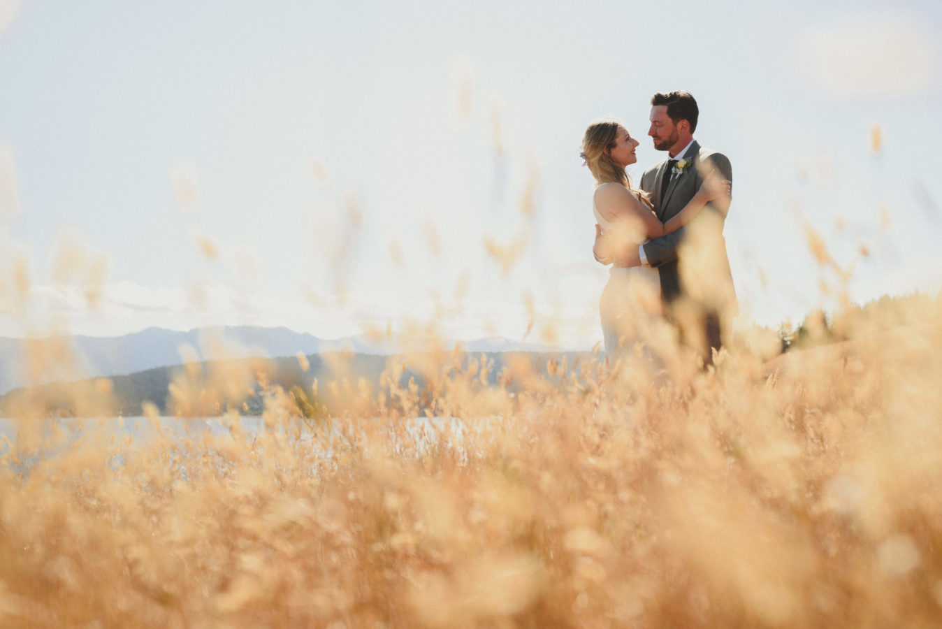 bride and groom embracing amongst the tall grass in a bluff overlooking the ocean
