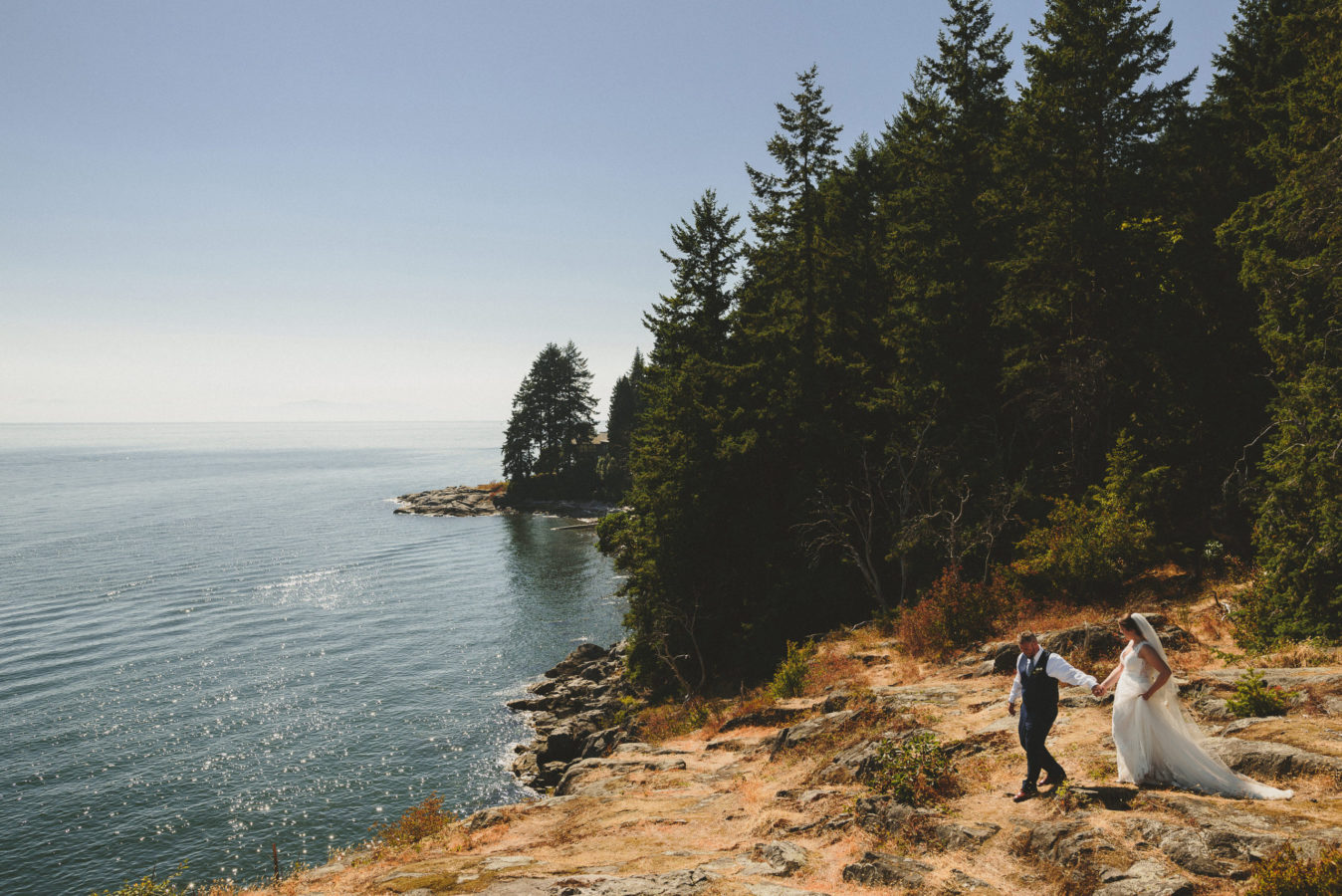 looking down on a bride and groom walking hand in hand out along a bluff overlooking the ocean