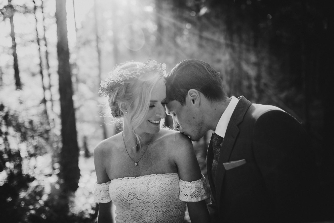 groom kissing his bride's shoulder in the sunlit forest on their wedding day