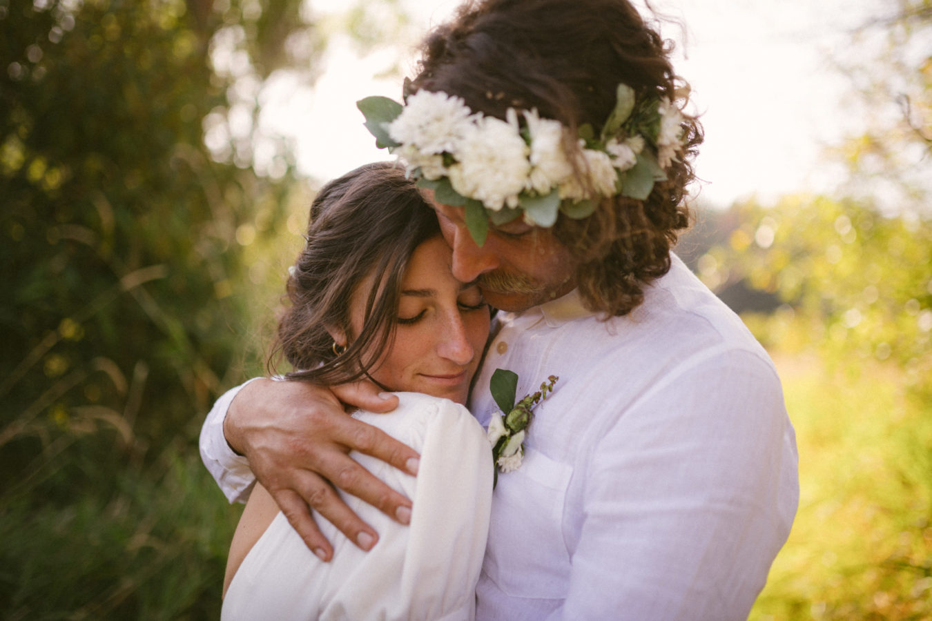 close up of a bride and groom intimately hugging on their wedding day with out of focus trees behind them