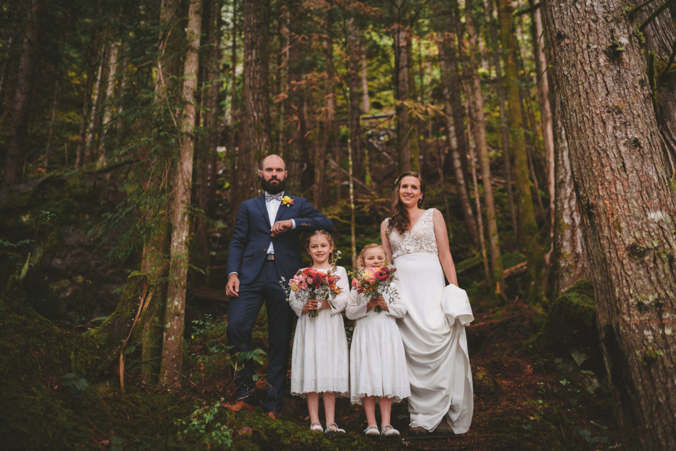 bride, groom and two flower girls standing among tall trees in the forest for a portrait