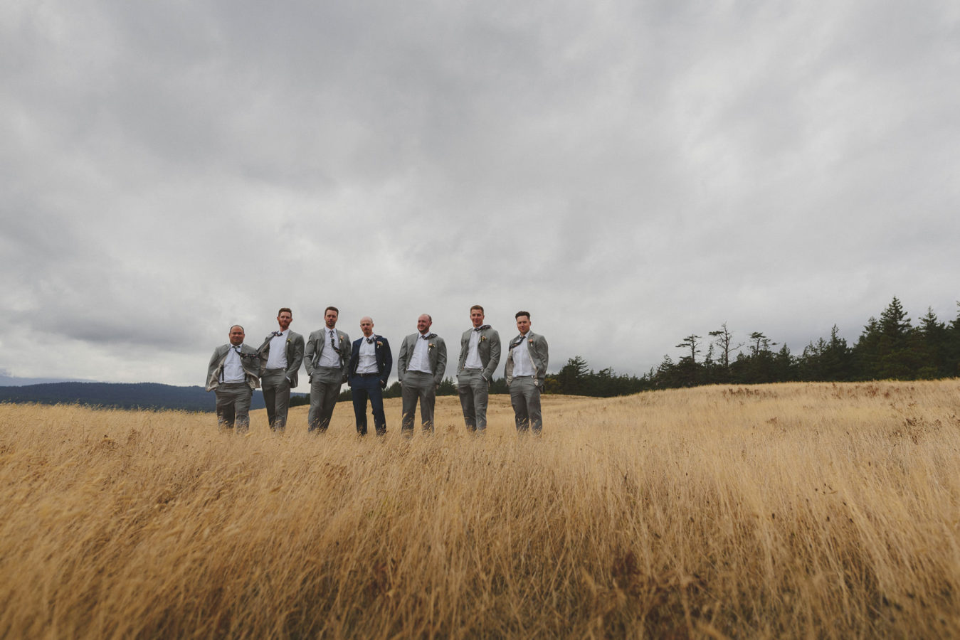 looking across a wind swept grassy field at a groom and size groomsmen standing for a portrait in the wind with a stormy sky above