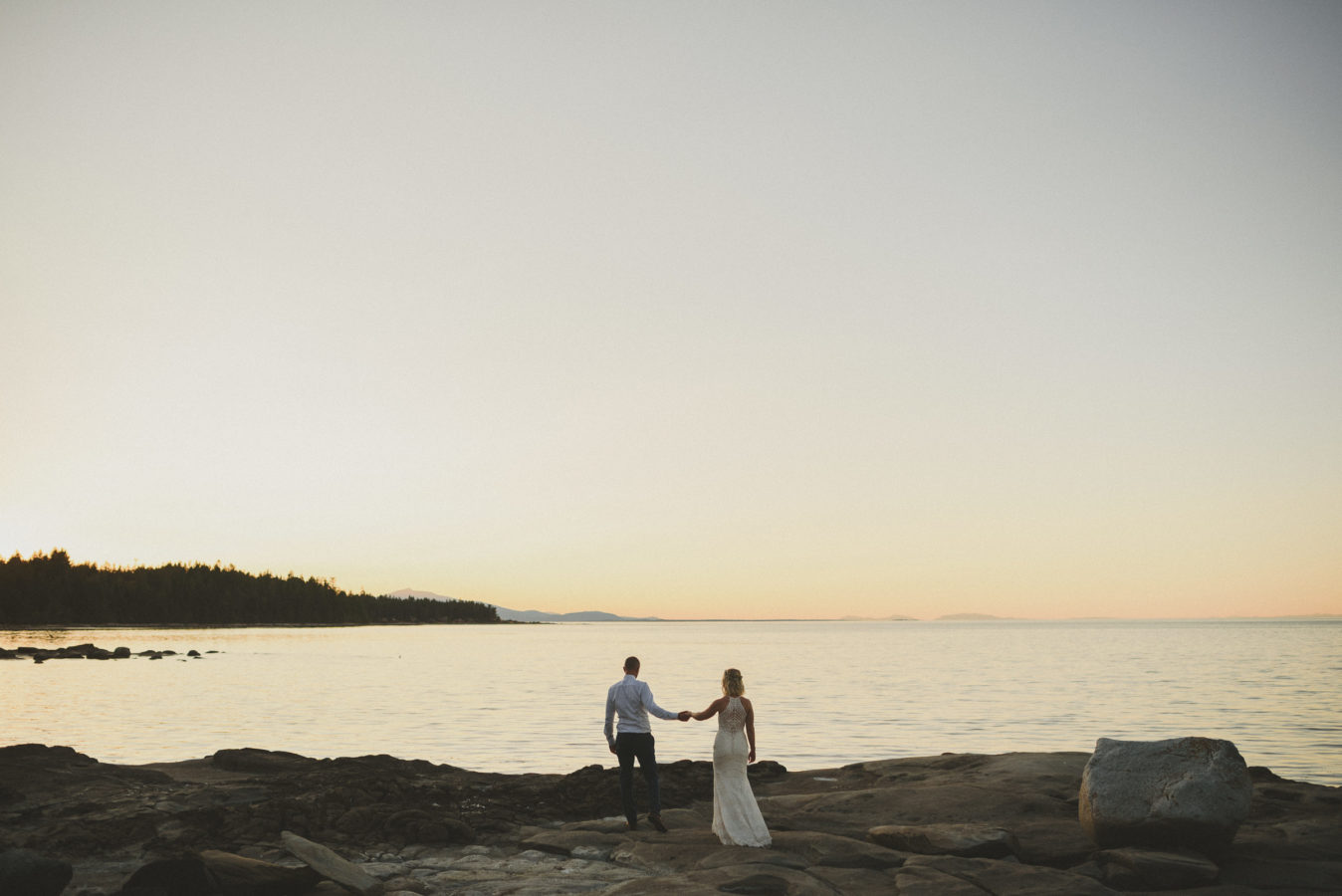 bride and groom holding hands and walking towards the ocean on a rocky shore at sunset