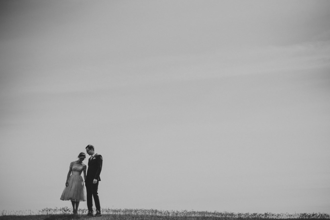 bride and groom leaning in on one another with a huge sky framing them