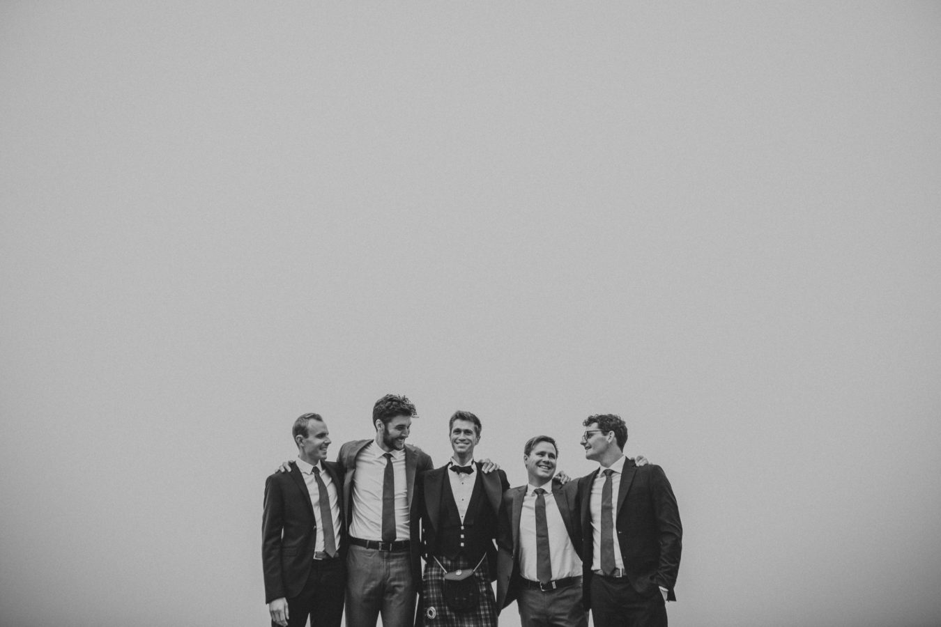 groom in a kilt with 4 groomsmen standing and laughing with a big foggy sky framing them