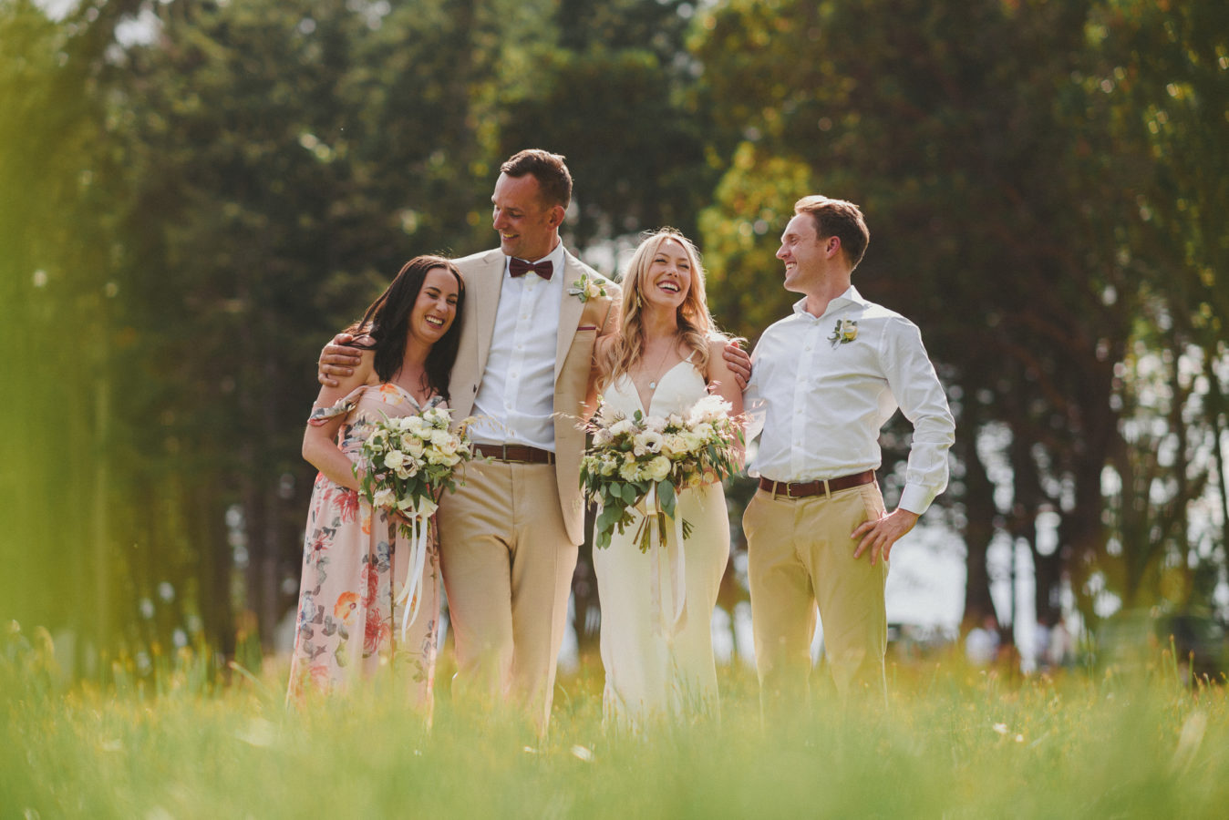 bride, groom and their maid-of-honour and best-man standing and laughing in a field of tall grass with the forest behind them
