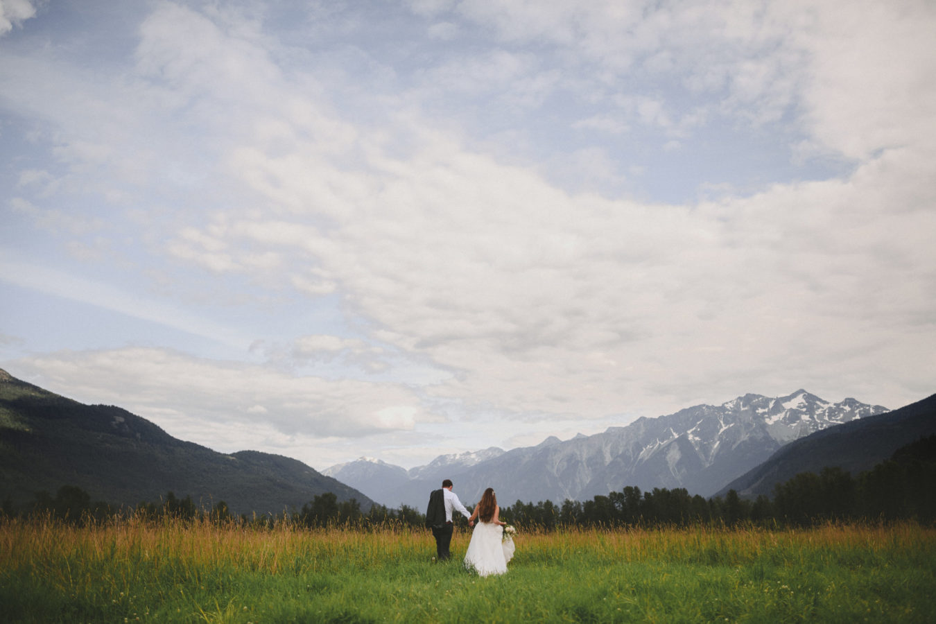 bride and groom walking in a huge field towards the mountains in front of them framed by a big sky