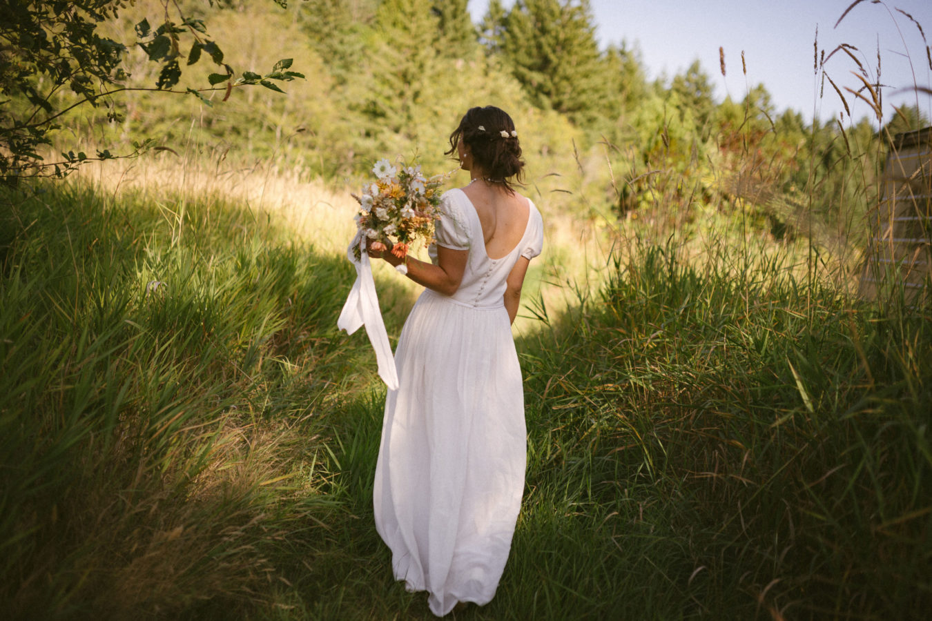 back of a bride in her wedding dress walking away in a field holding her bouquet of flowers