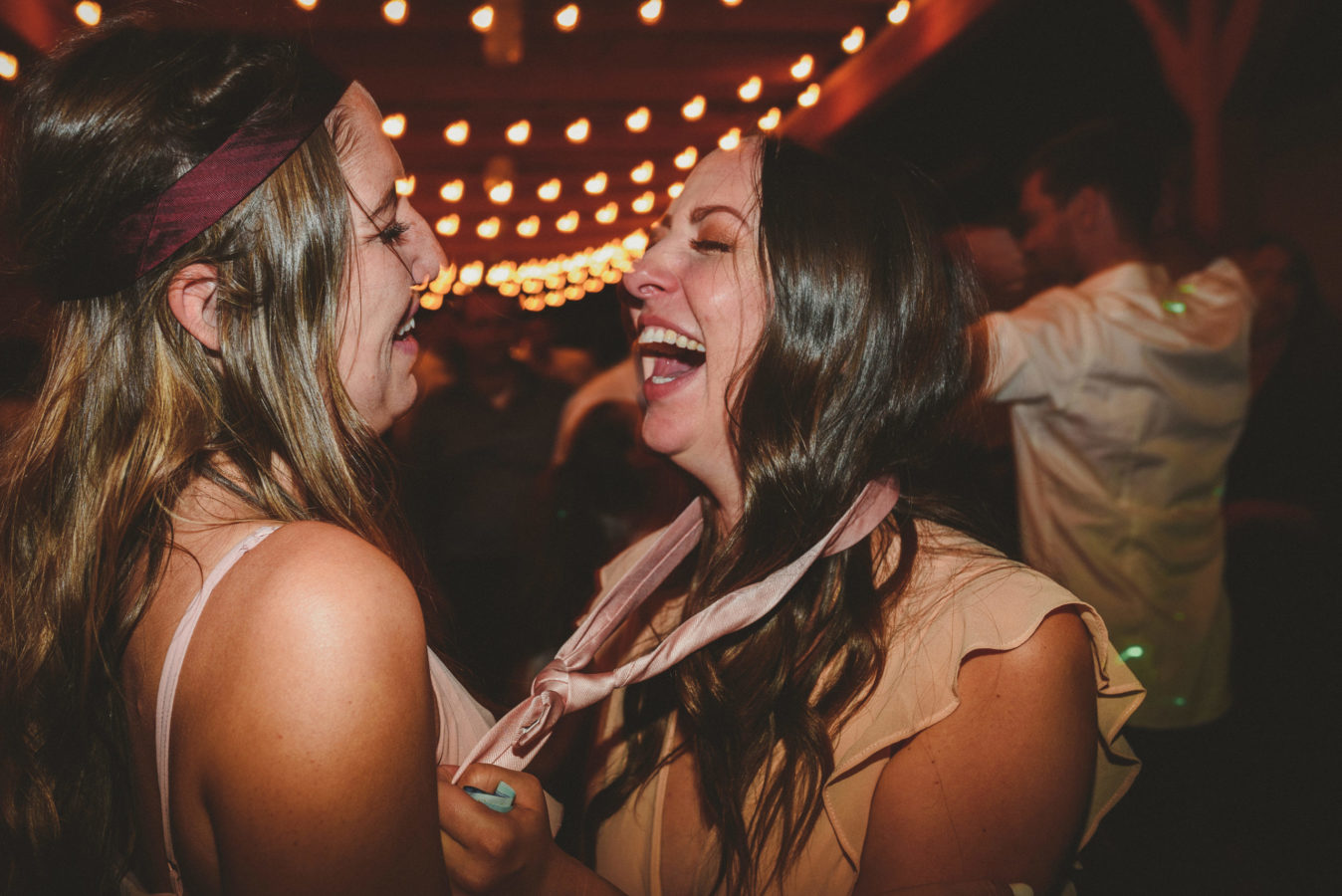two bridesmaids laughing on the dance floor at a wedding