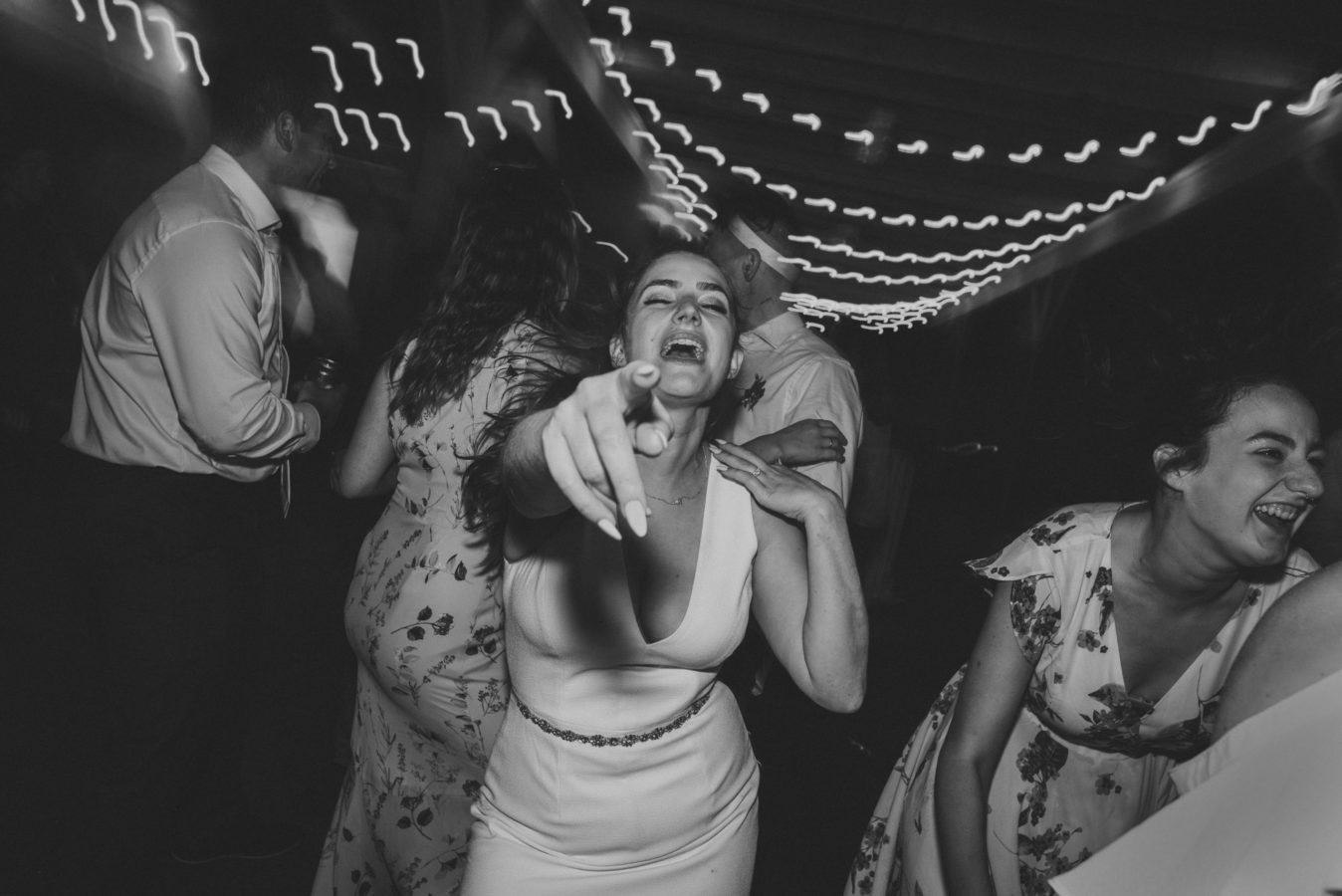 bride dancing and pointing at the camera on the dance floor on her wedding day