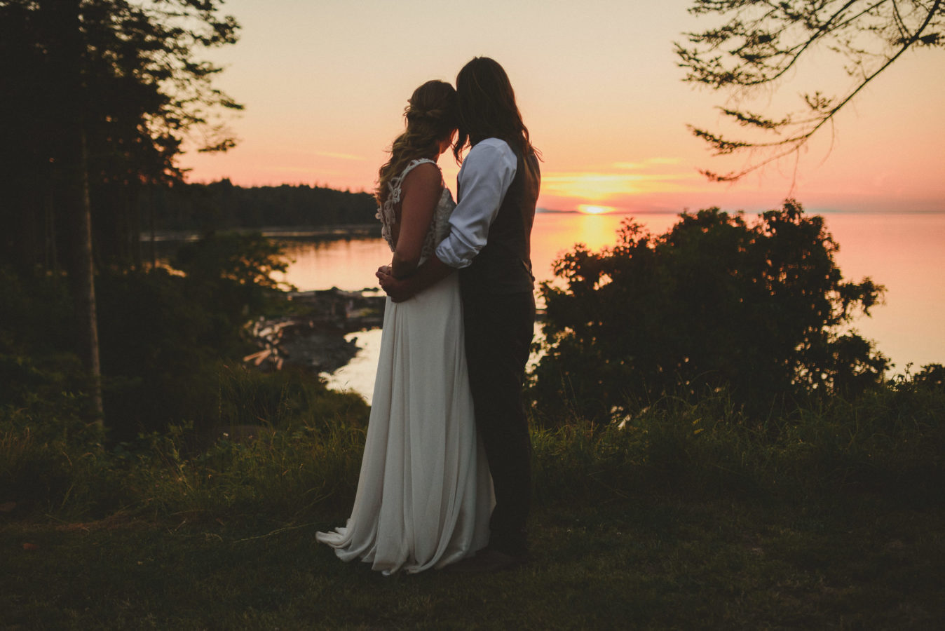 bride and groom hugging looking out at the setting sun over a bay