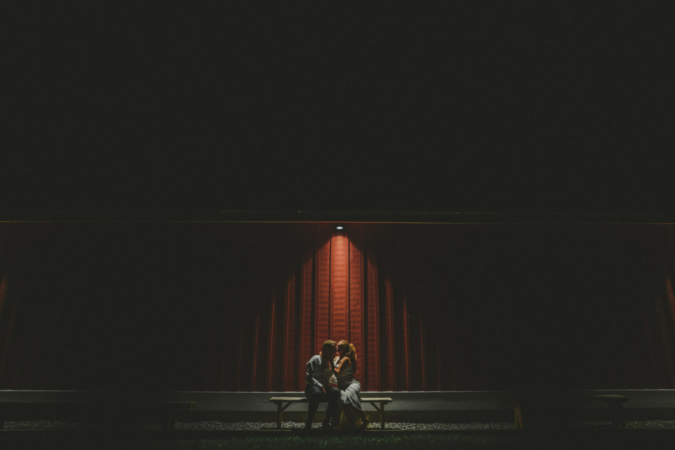 bride and groom at night on a bench next to a red barn with one light shining down upon them