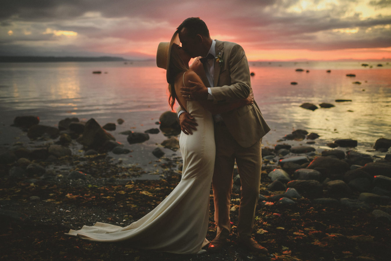 bride and groom kissing in a deep embrace on the edge of a rocky beach at sunset