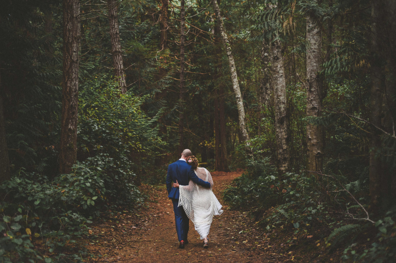 bride and groom walking arm in arm down a forest path surrounded by tall trees