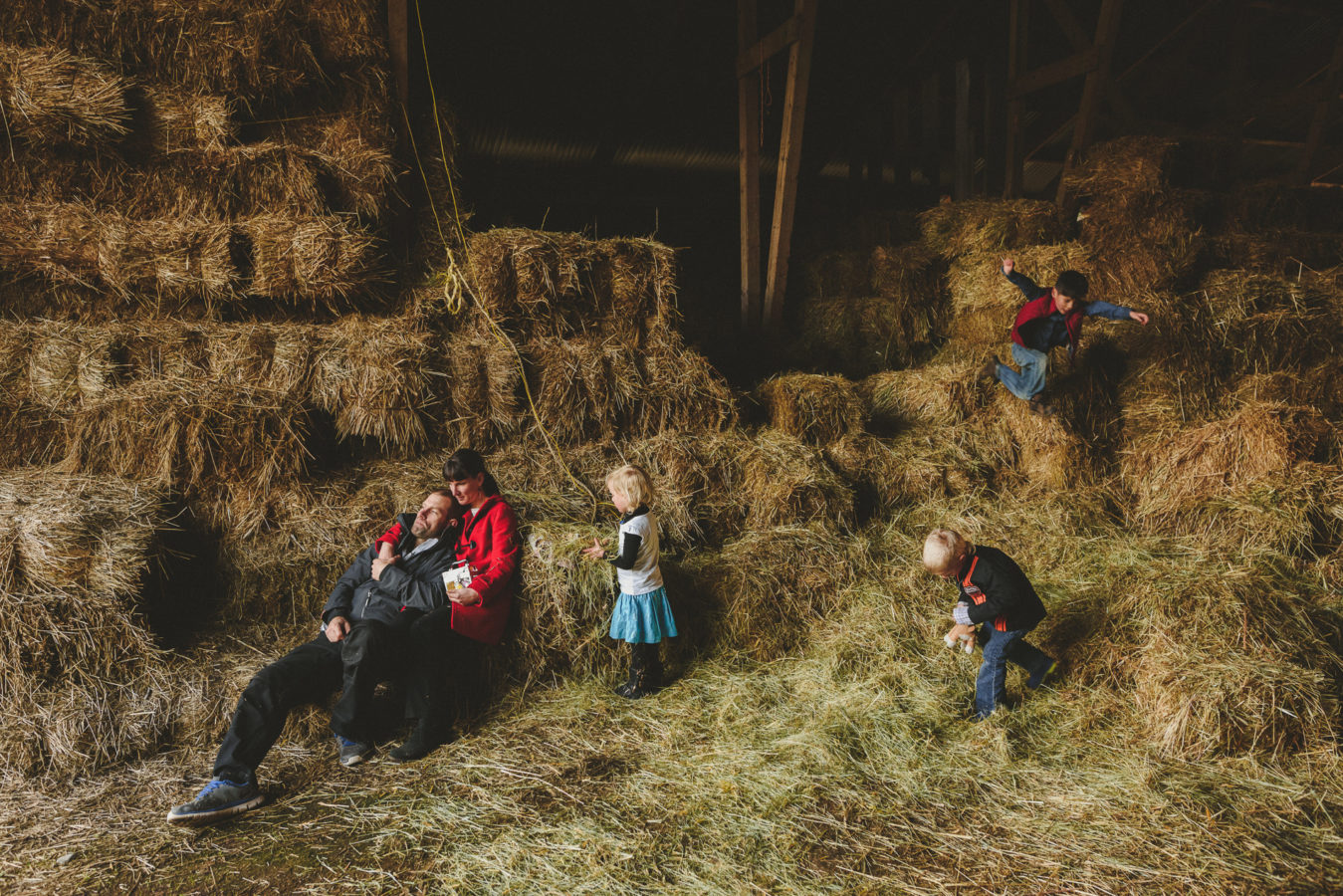 family amongst the hay bails in a bar with one kid jumping in the air