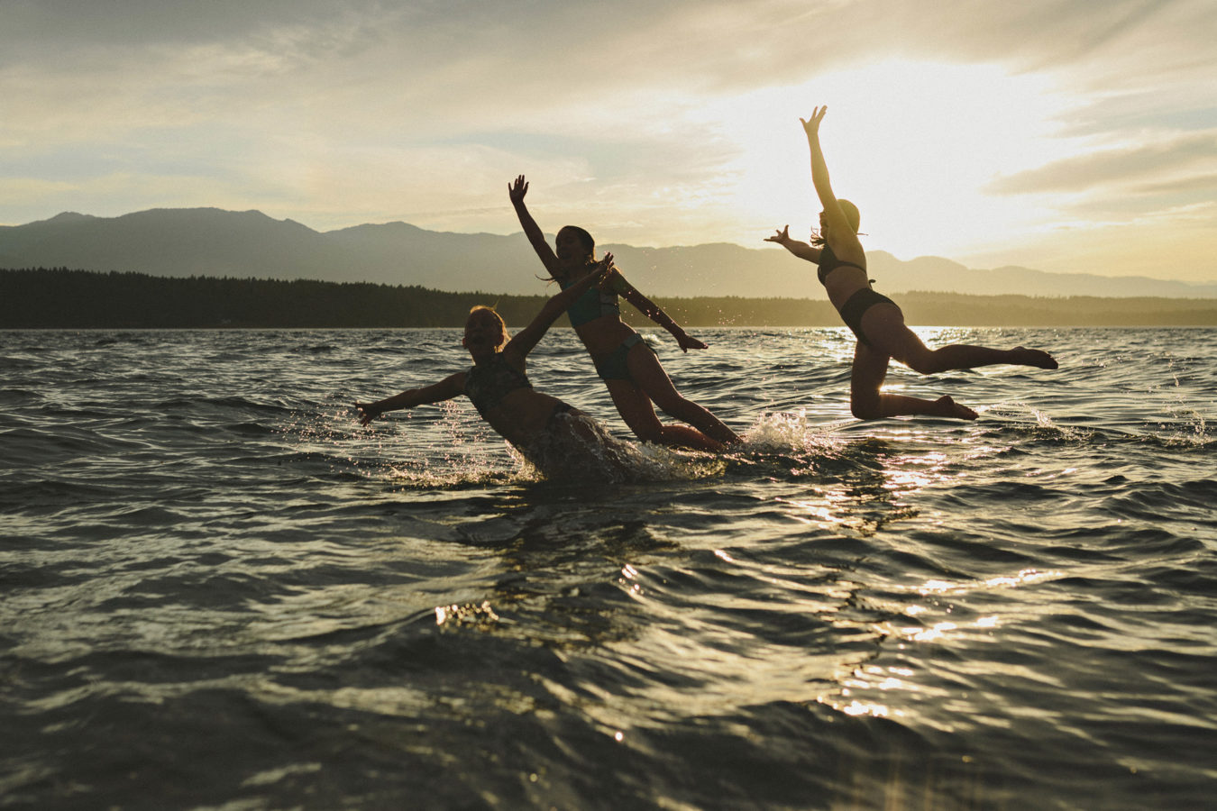 three older kids jumping into the ocean with the sun setting behind them