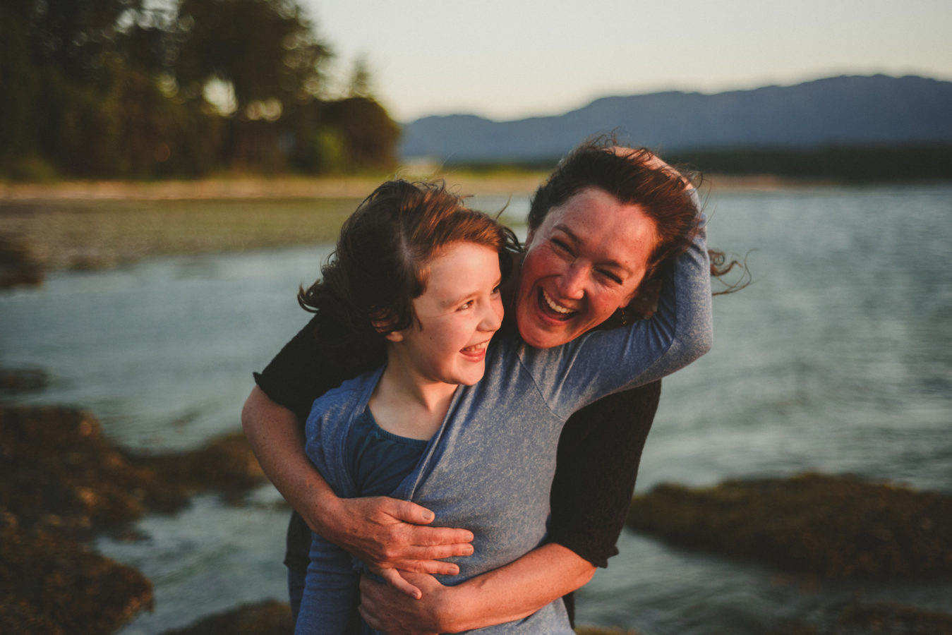mom and daughter snuggling and laughing in the sunset light by the ocean