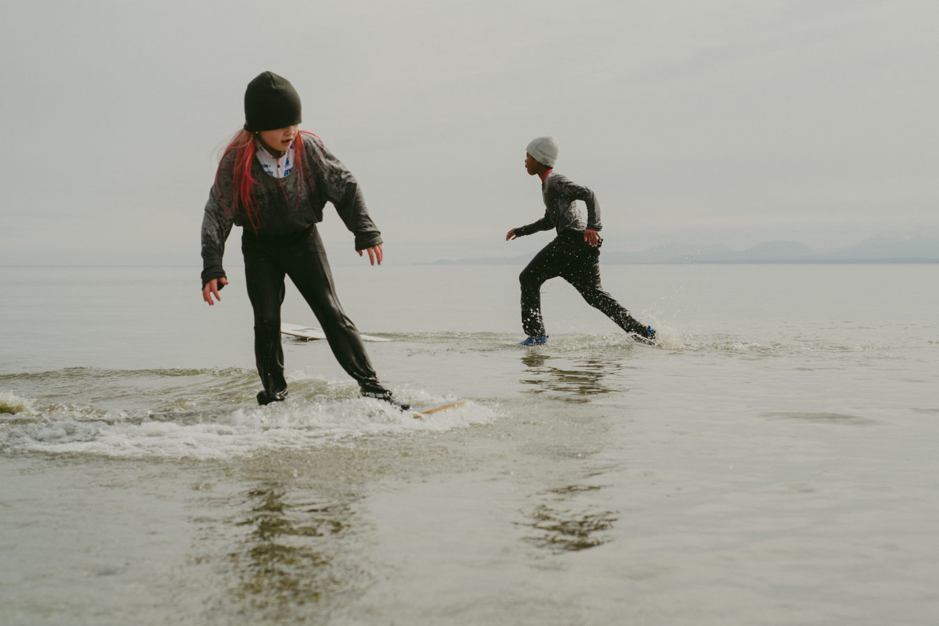 two kids skim boarding in winter clothes and toques