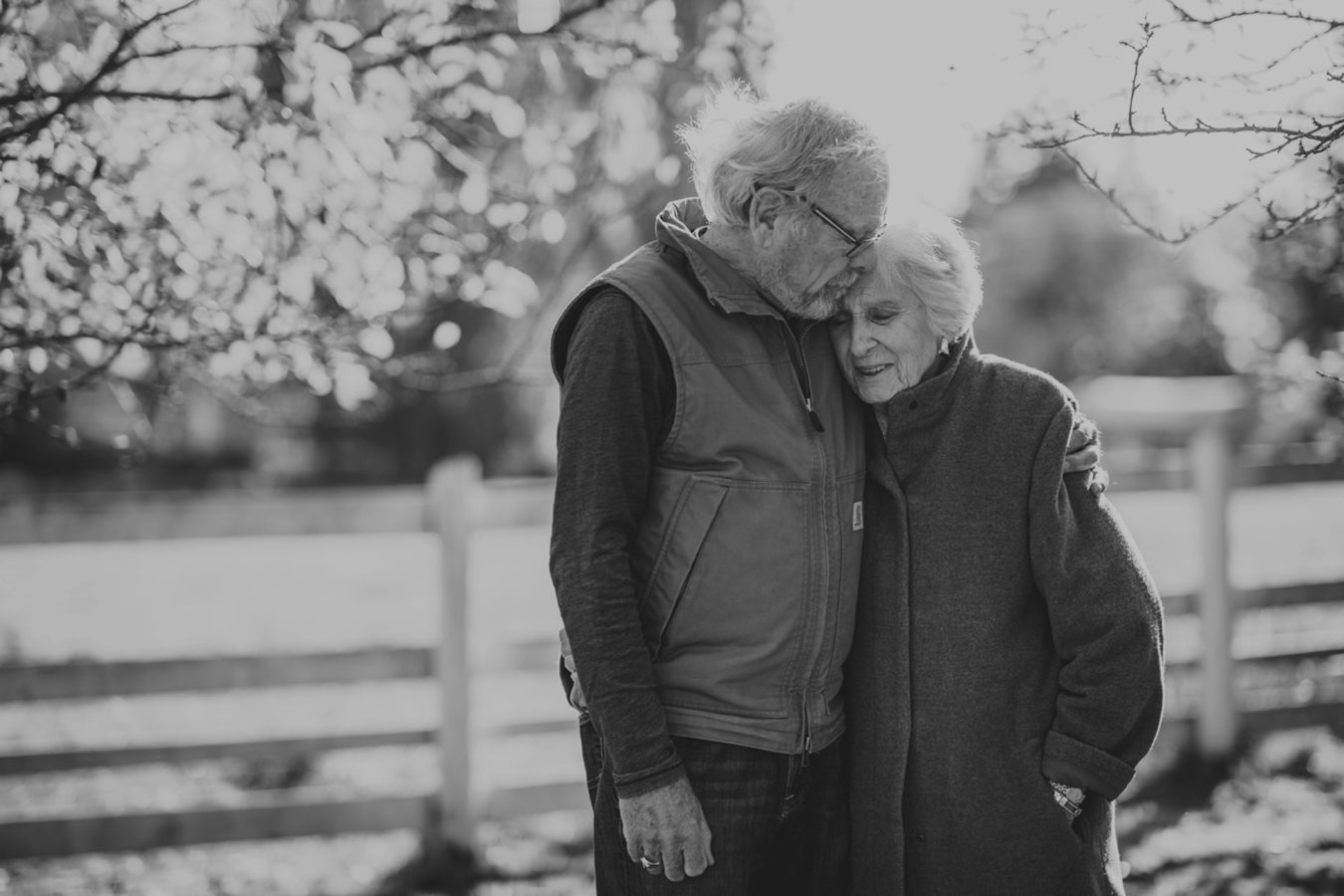an elderly couple intimately embracing by a rustic fence and fruit tree