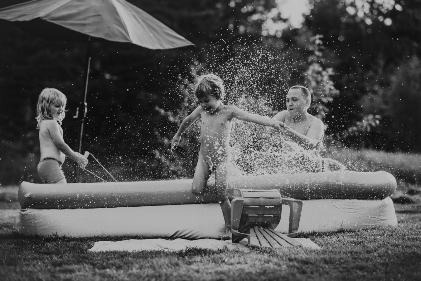 three kids splashing and playing in a small outdoor pool