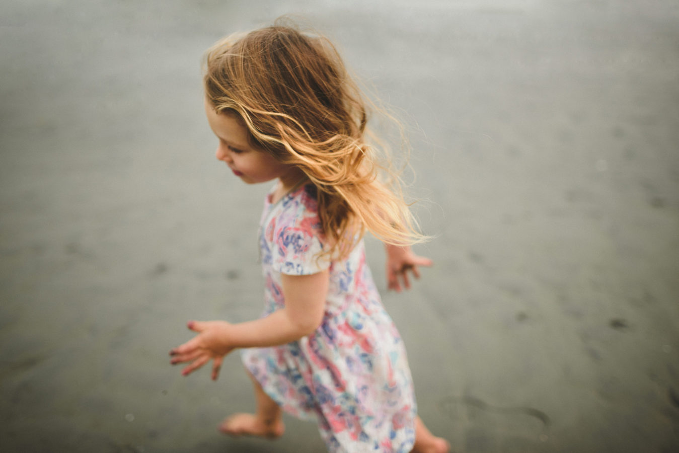 little girl running on the beach with her hair tossed behind her
