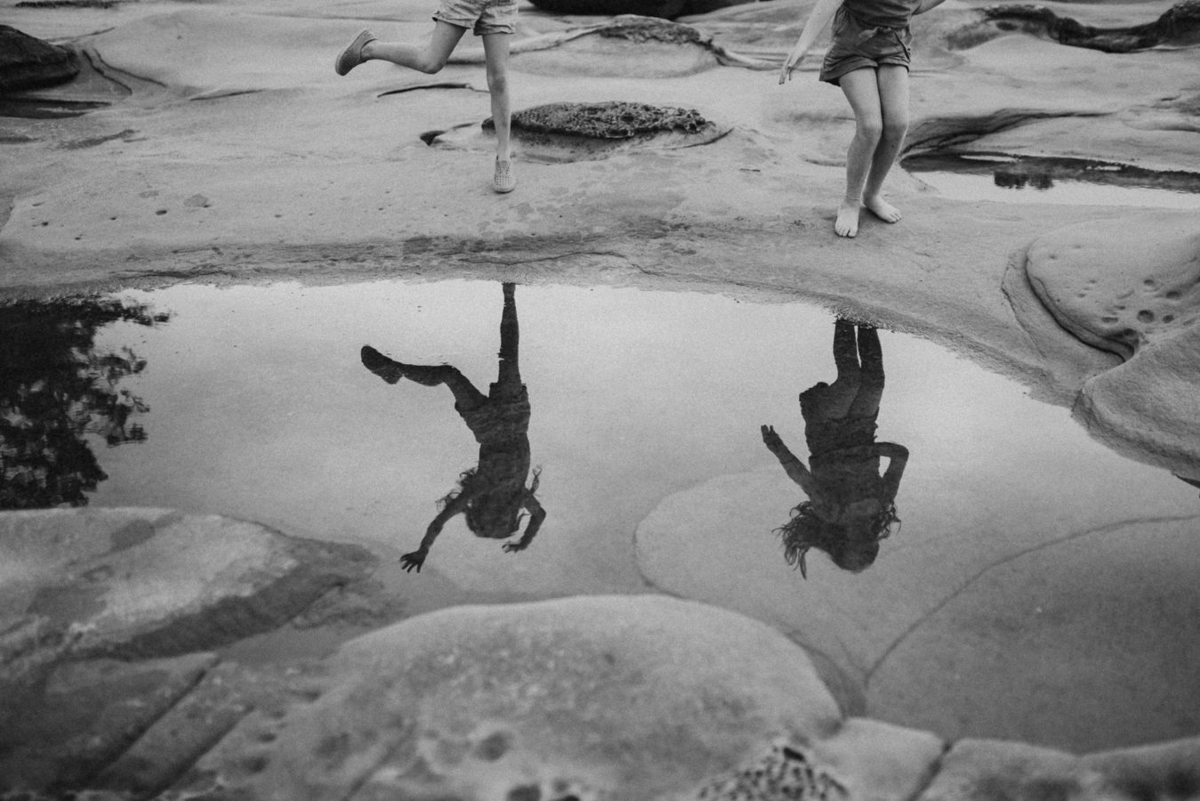 reflection of two kids dancing beside a tidal pool