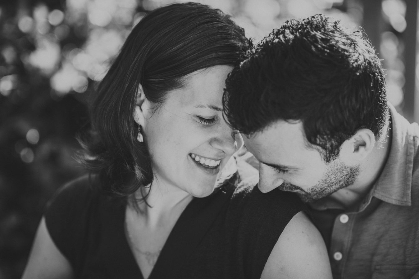 man kissing his wife's shoulder in a sweet intimate moment