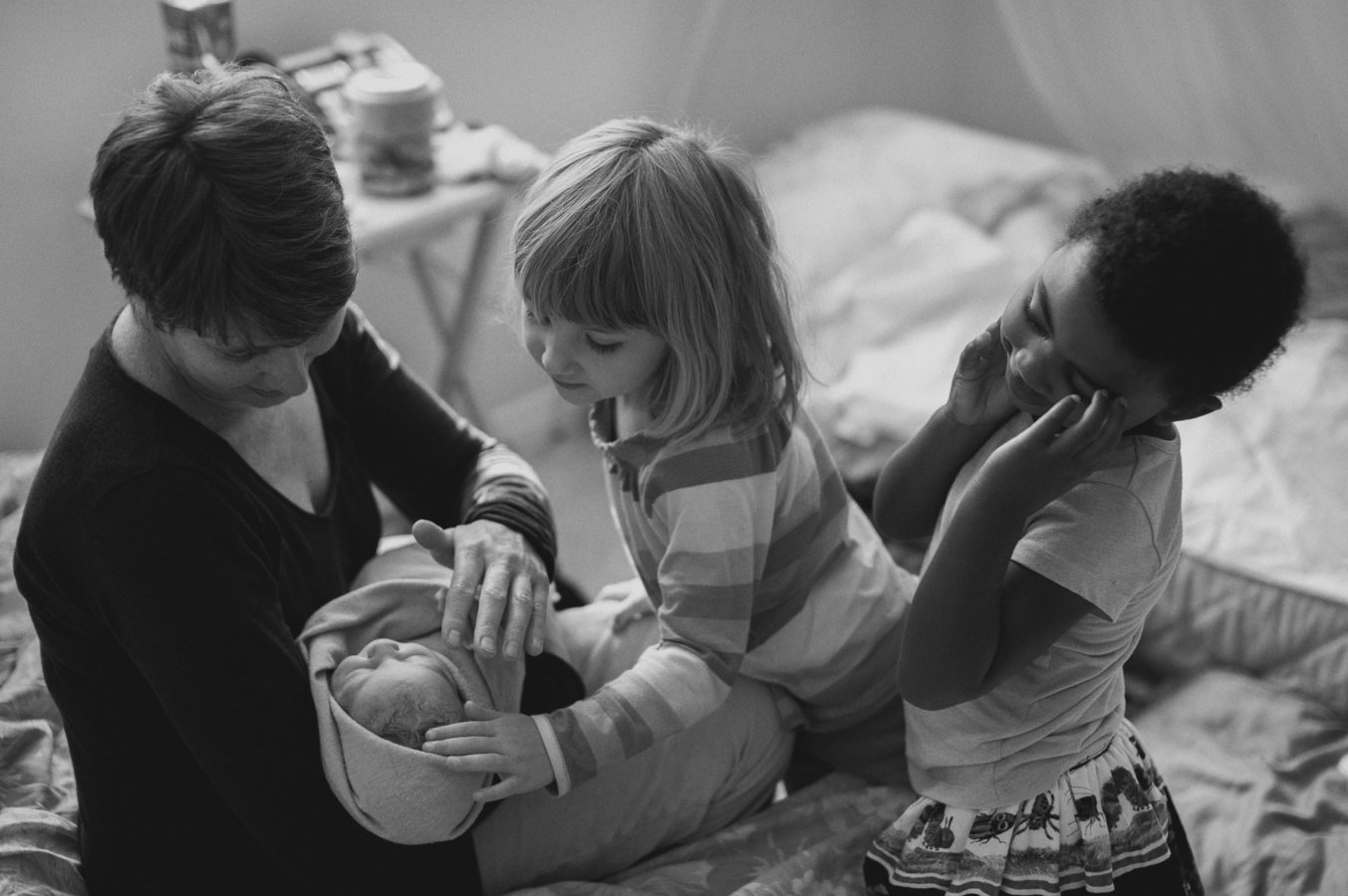 2 kids looking amazed at a young grandmother holding a brand new baby