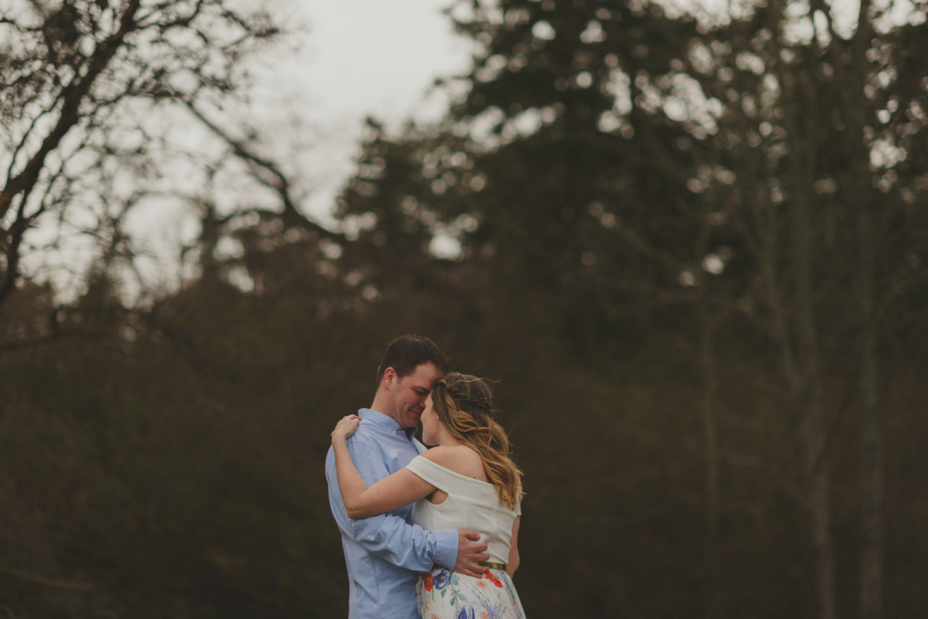 engaged couple snuggling against the dark trees