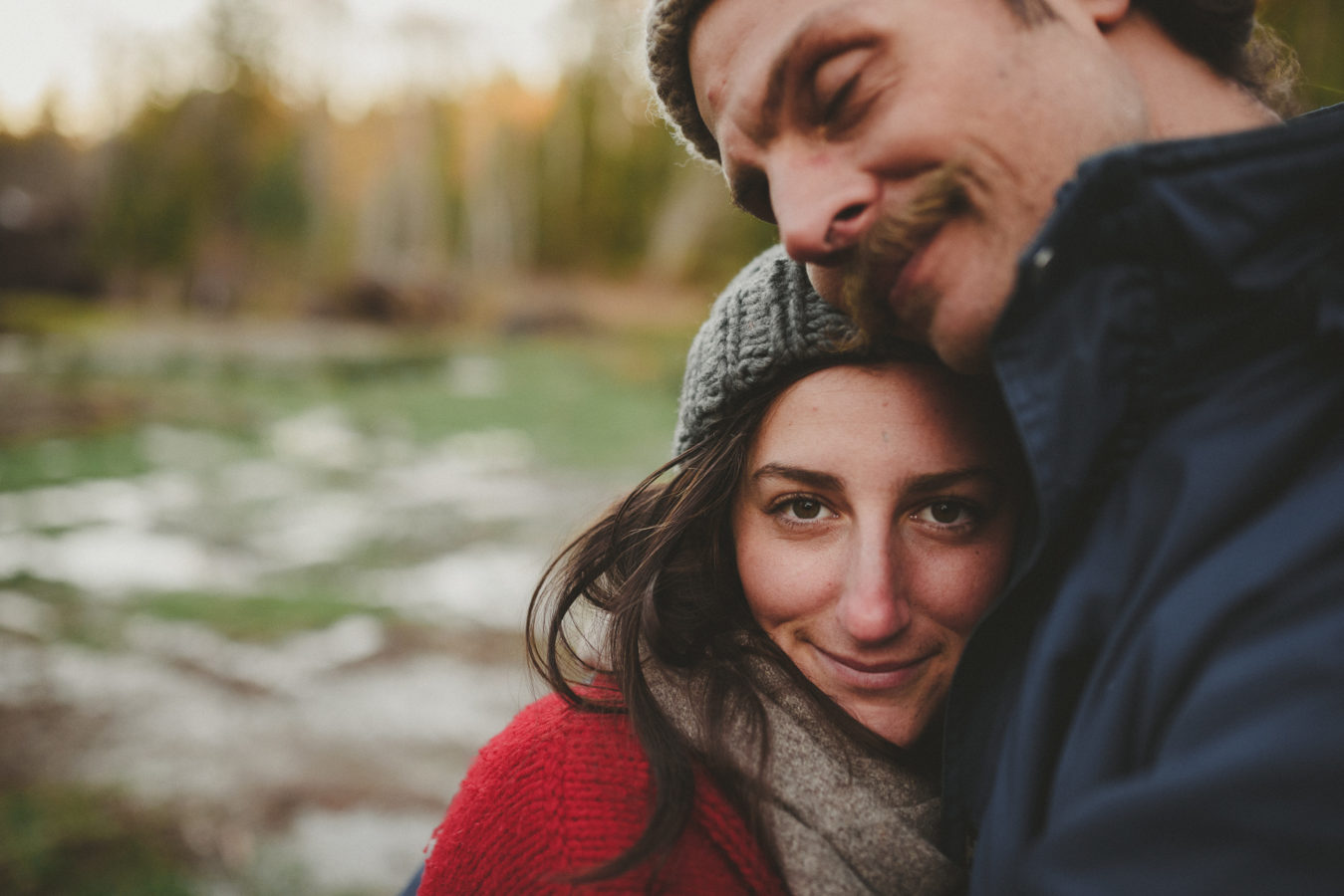 young woman snuggled into her man smiling at the camera