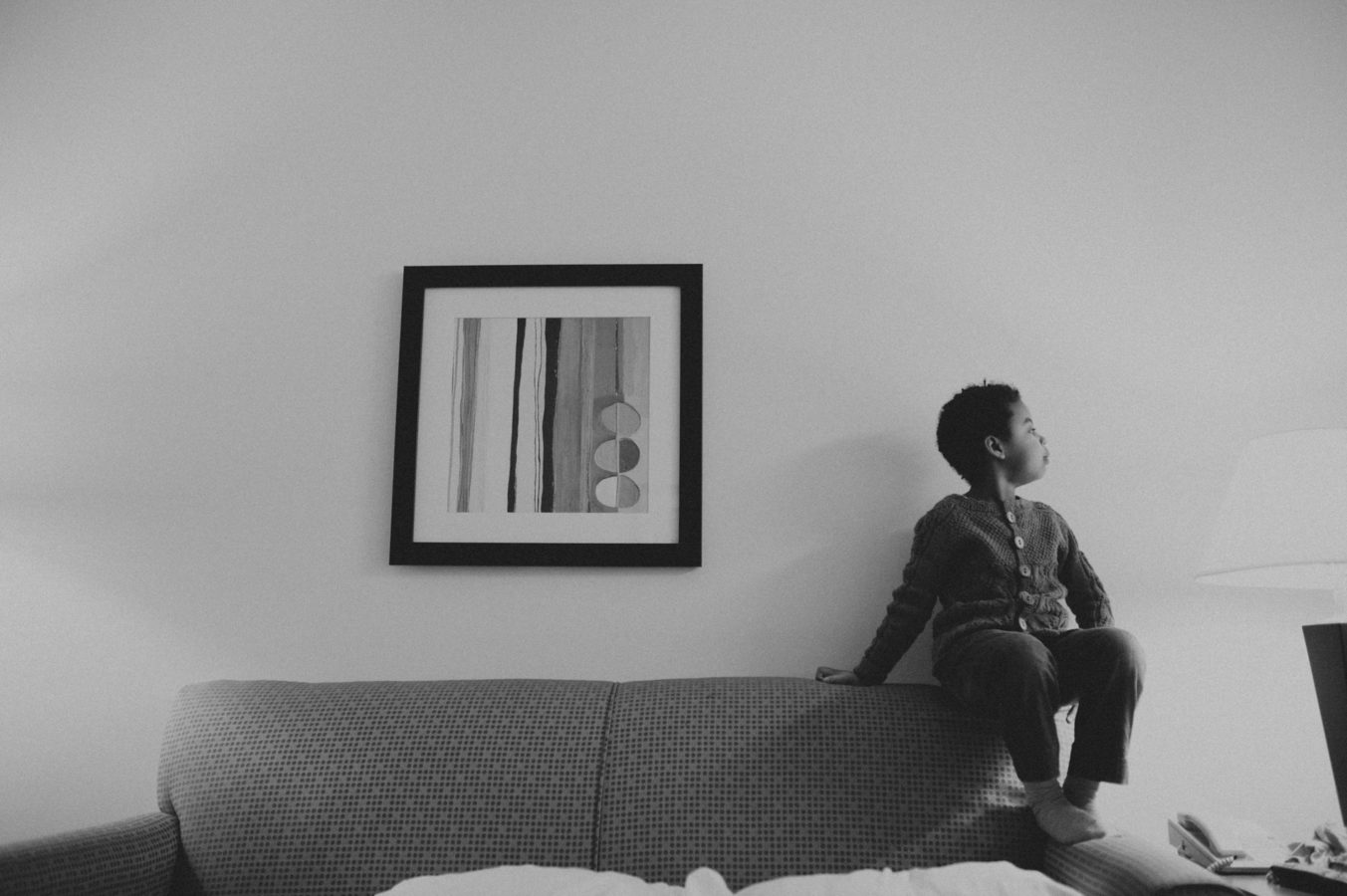 young Black girl sitting on the arm of a couch with a painting beside her on the wall