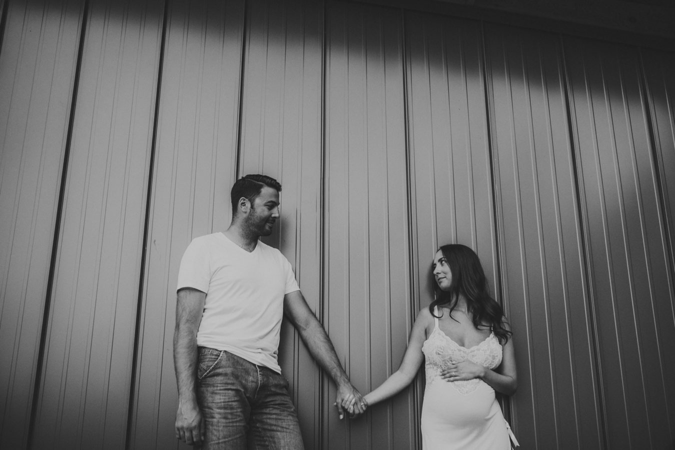 pregnant woman and her husband leaning up against a metal wall holding hands
