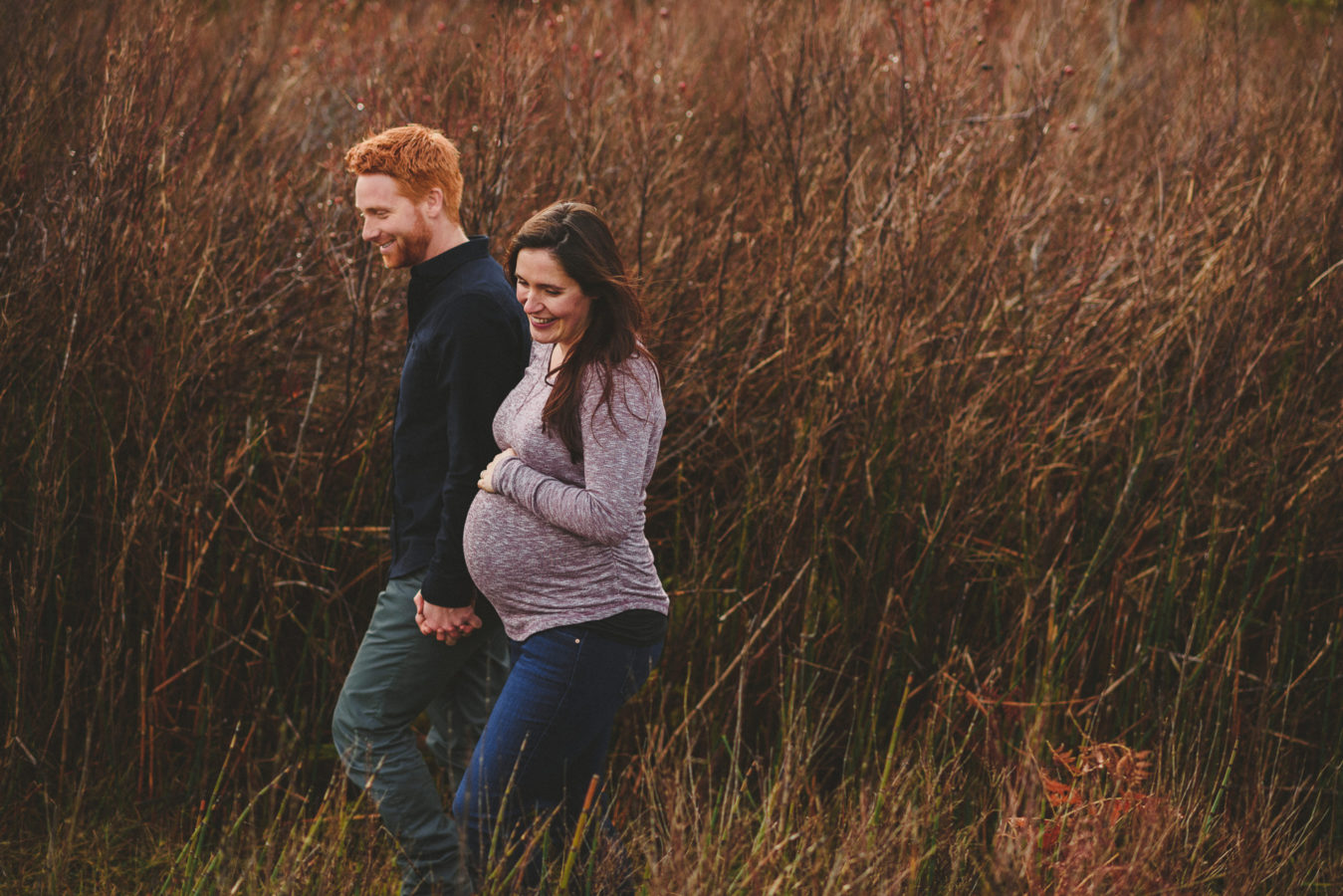 pregnant woman and her husband holding hands as the walk along a path lined with tall beach grass