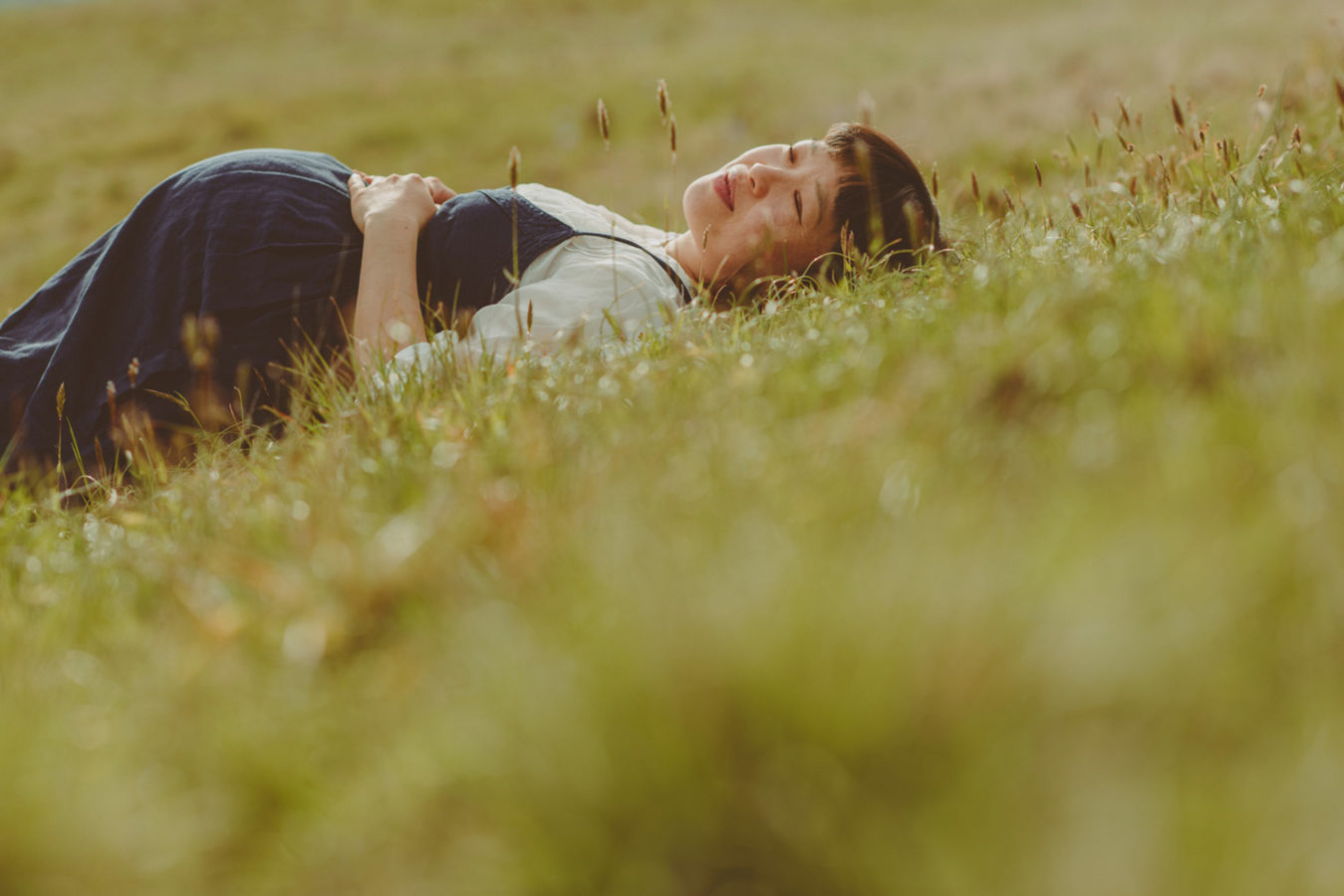 pregnant woman lying in the tall grass