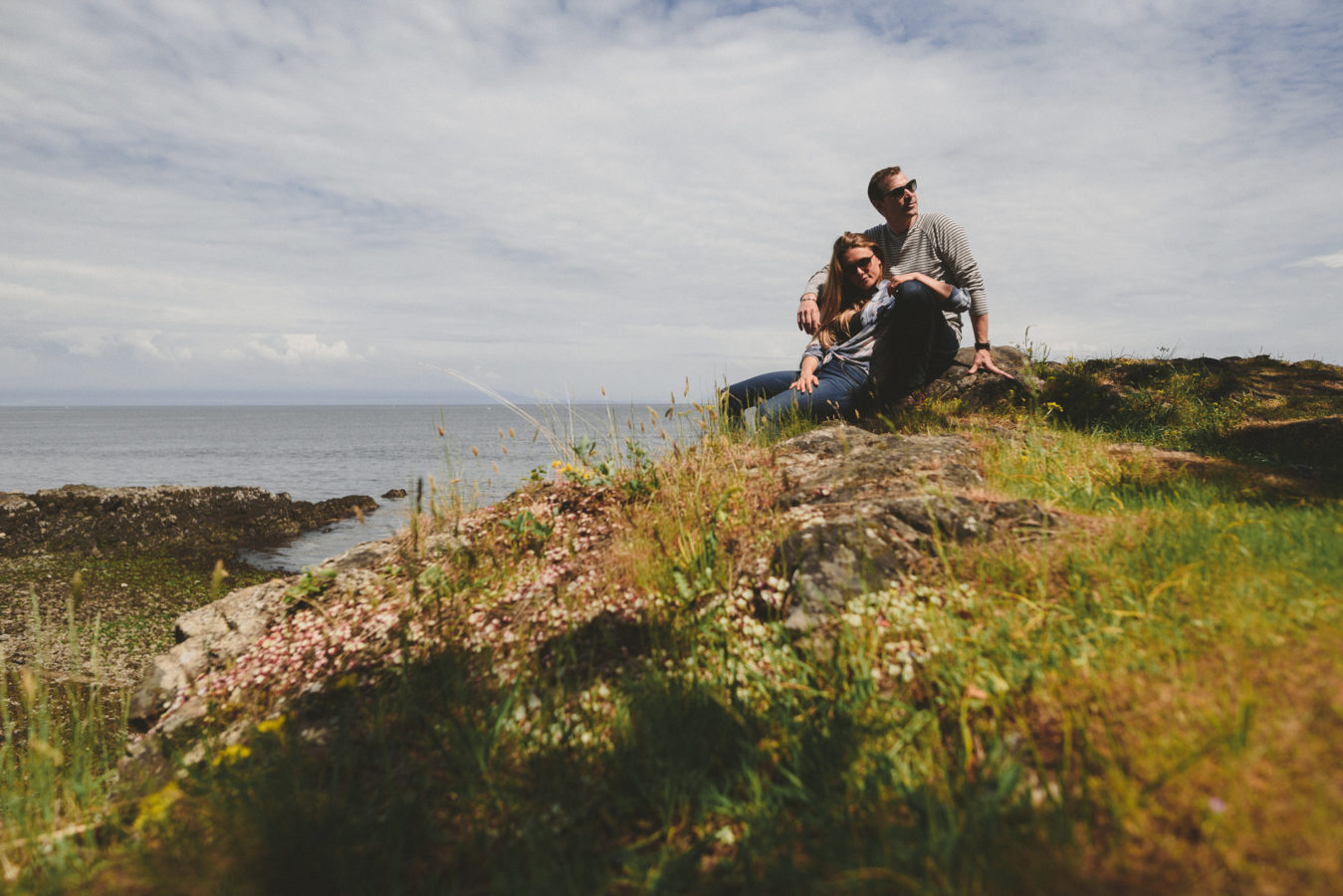 man and woman sitting and snuggling on a rocky bluff overlooking the ocean