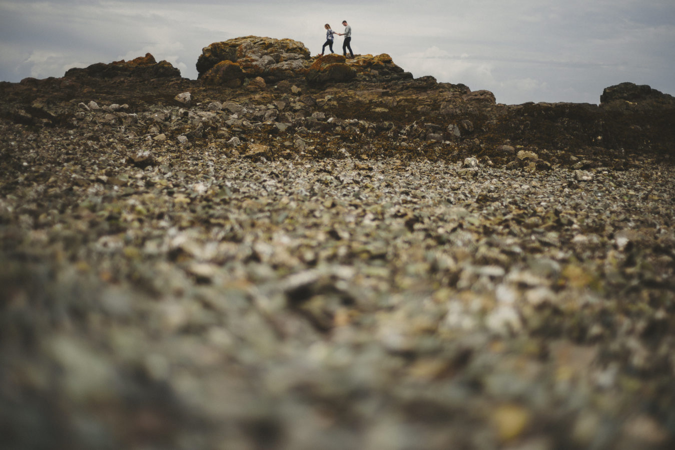 couple walking along a rocky area on the beach with the beach out of focus in the foreground