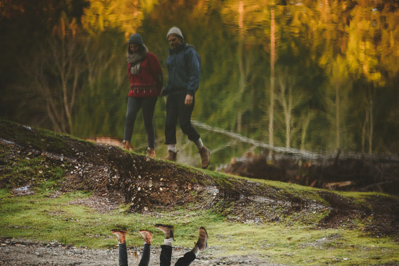 upside down photo of a couple walking along the edge of a pond