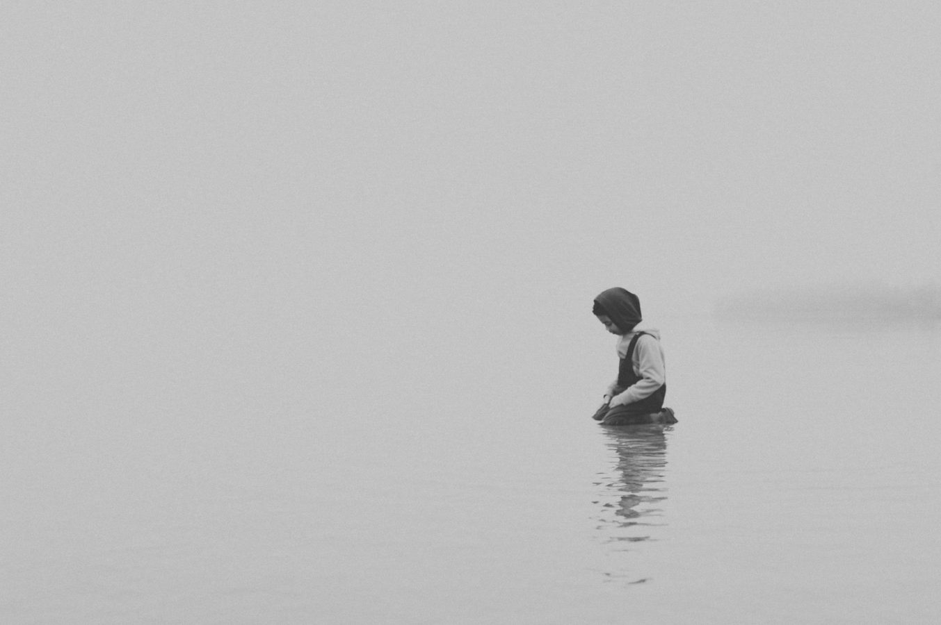 a lone child kneels in the calm ocean wearing a toque and rain pants in the fog