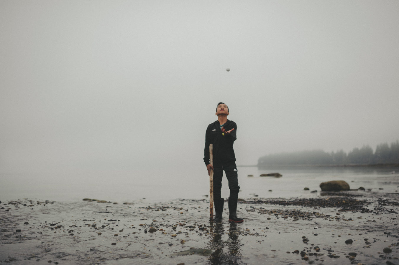 photo of a boy tossing a rock in the air on a foggy beach