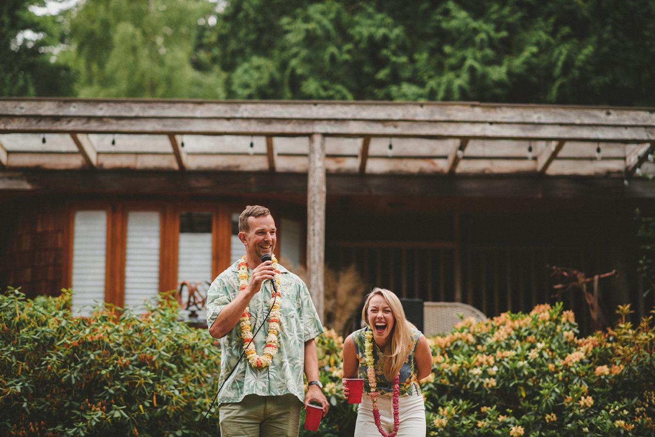 man talking into a microphone and his wife laughing beside him in front of a west coast home