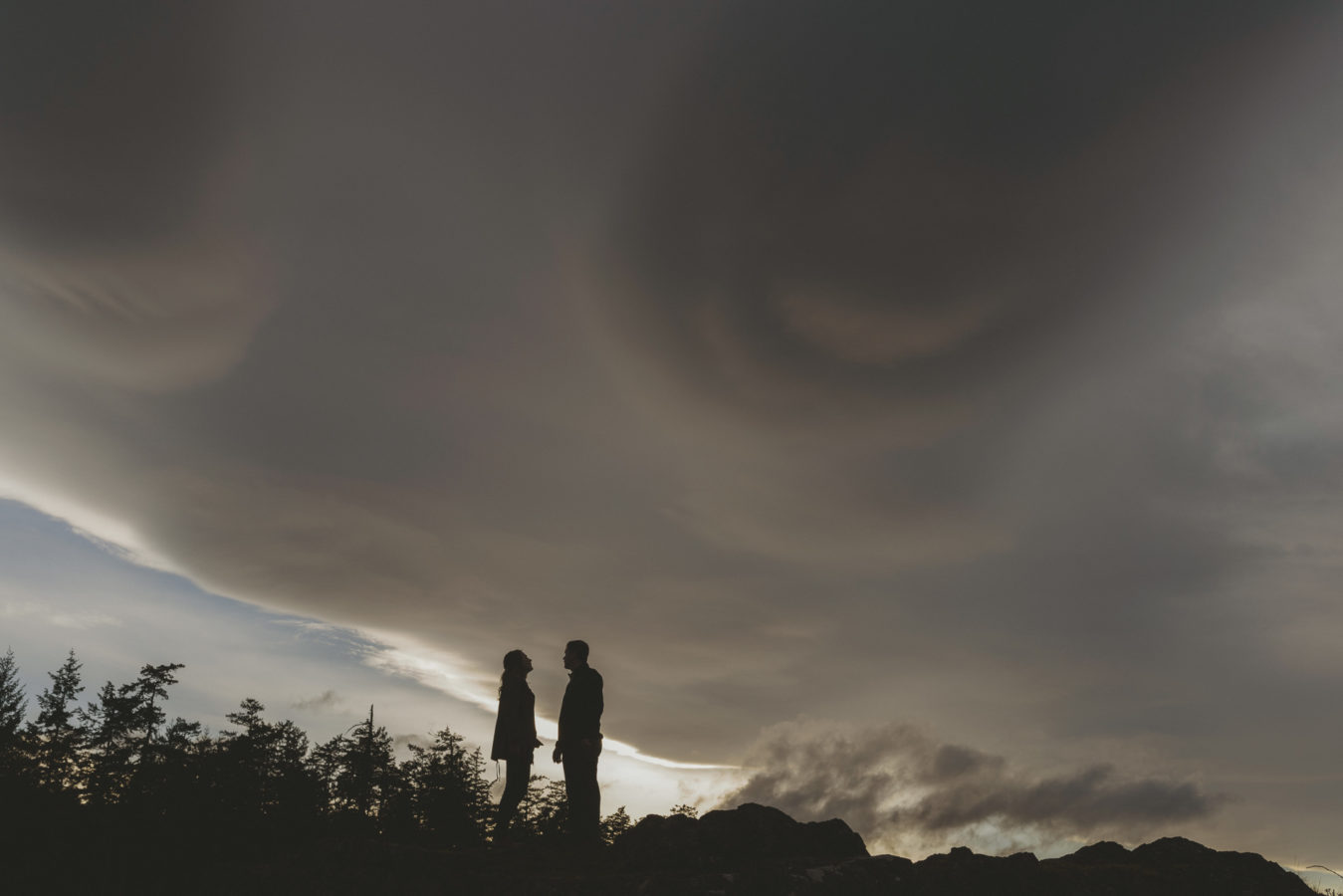 man and woman standing on a rocky bluff with a dark dramatic sky behind them