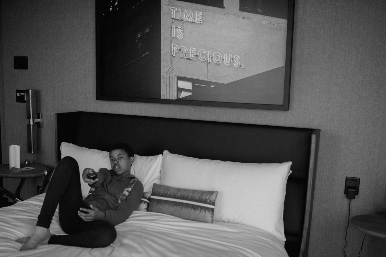kid lying on a hotel bed pointing the remote at the tv with a large framed photo on the wall behind them that reads Time is Precious
