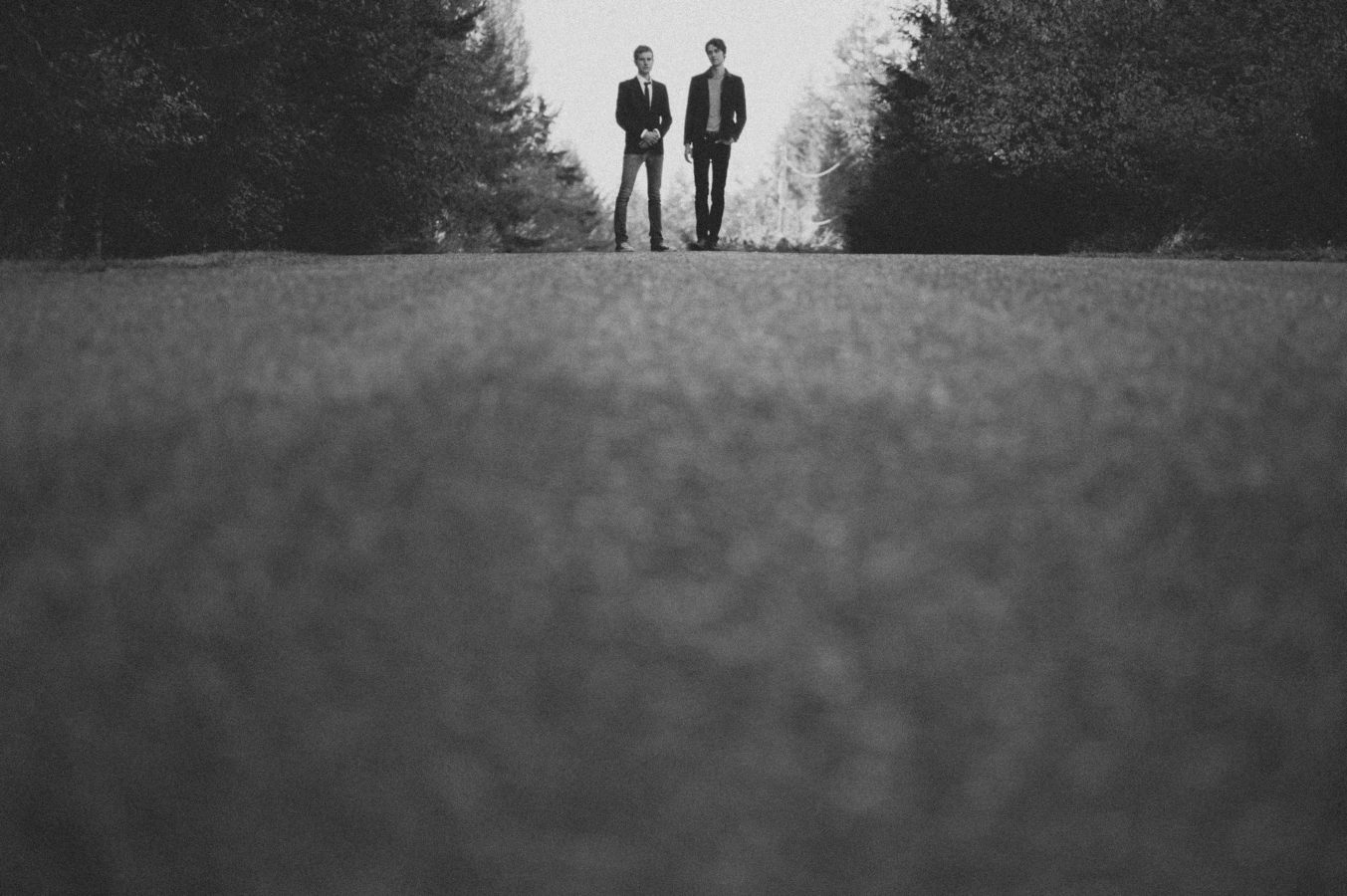 looking up a rural road at two men standing on the crest of a hill with the forest on either side of them