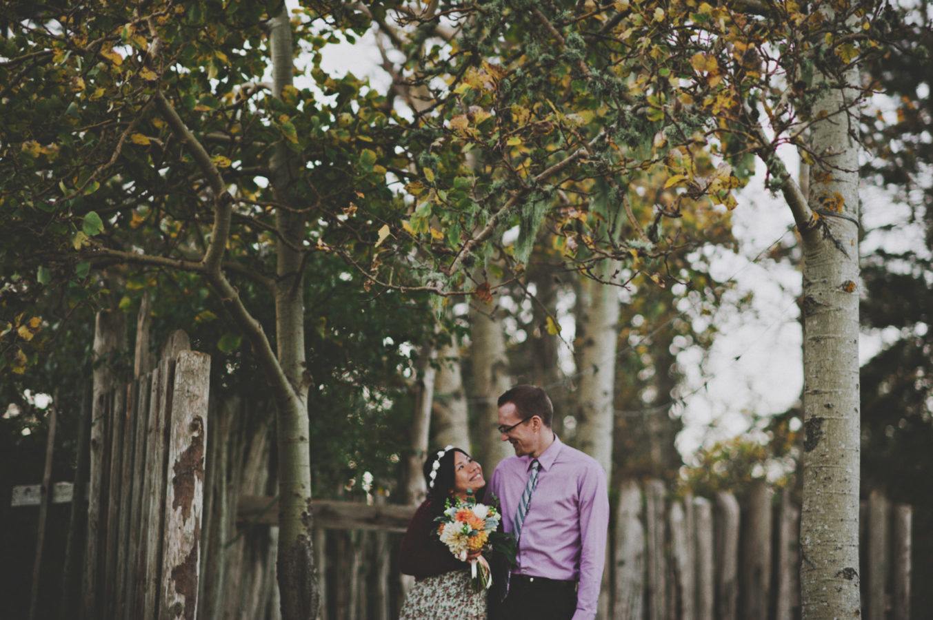 mixed race couple standing in front of a rustic fence smiling at one another on their wedding day
