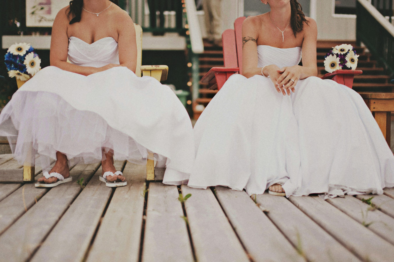 detail of two brides' dresses and shoes sitting on chairs on a deck