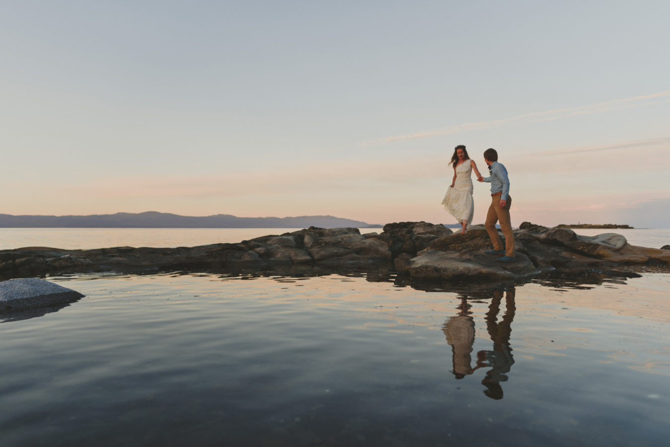 bride and groom walking along sandstone rocks in the water at sunset