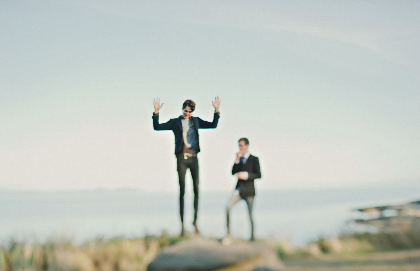 two grooms on a bluff by the ocean with one of them jumping in the air