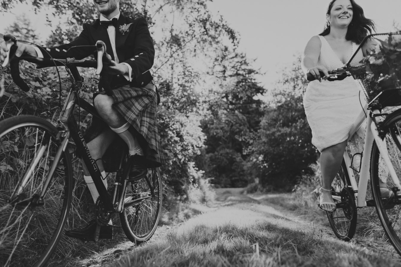 bride and groom riding their bikes towards the camera