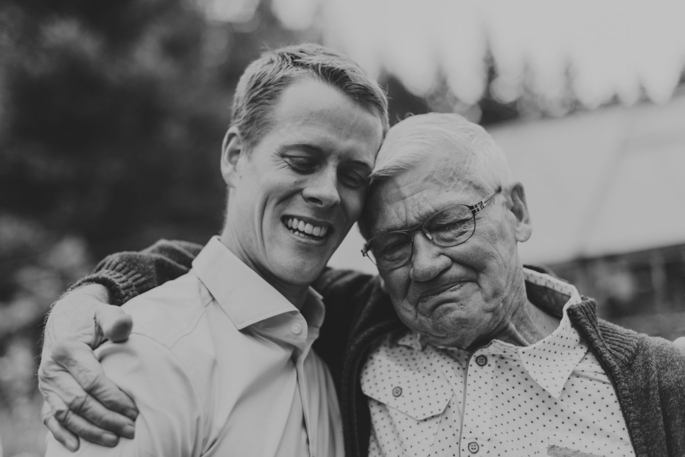 grandfather emotionally hugging his grandson on his wedding day