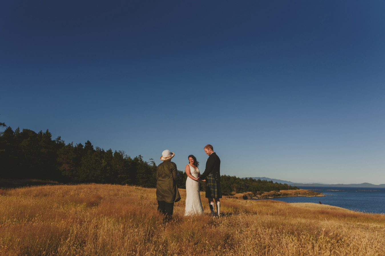 a bride and groom and officiant at their elopement ceremony on a grassy bluff overlooking the ocean